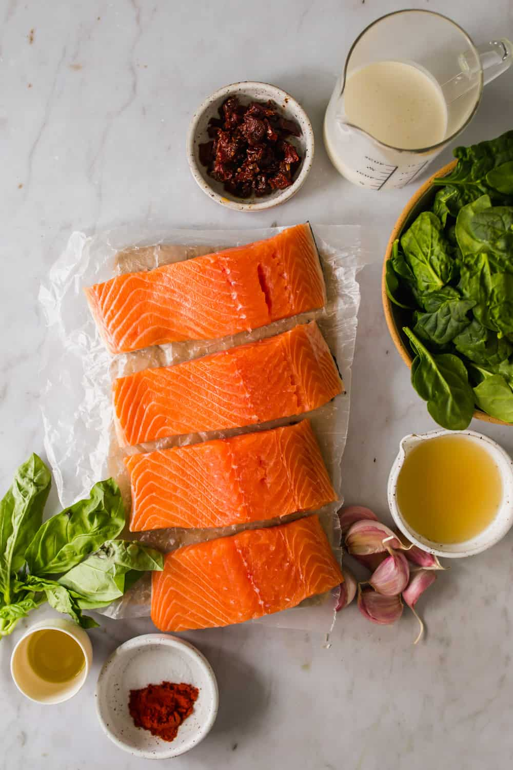 raw salmon filets on parchment paper next to bowls of salmon, broth, garlic, spices, and herbs