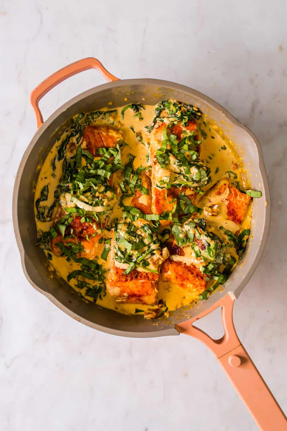 Cooked salmon and cream sauce topped with spinach in a large pan