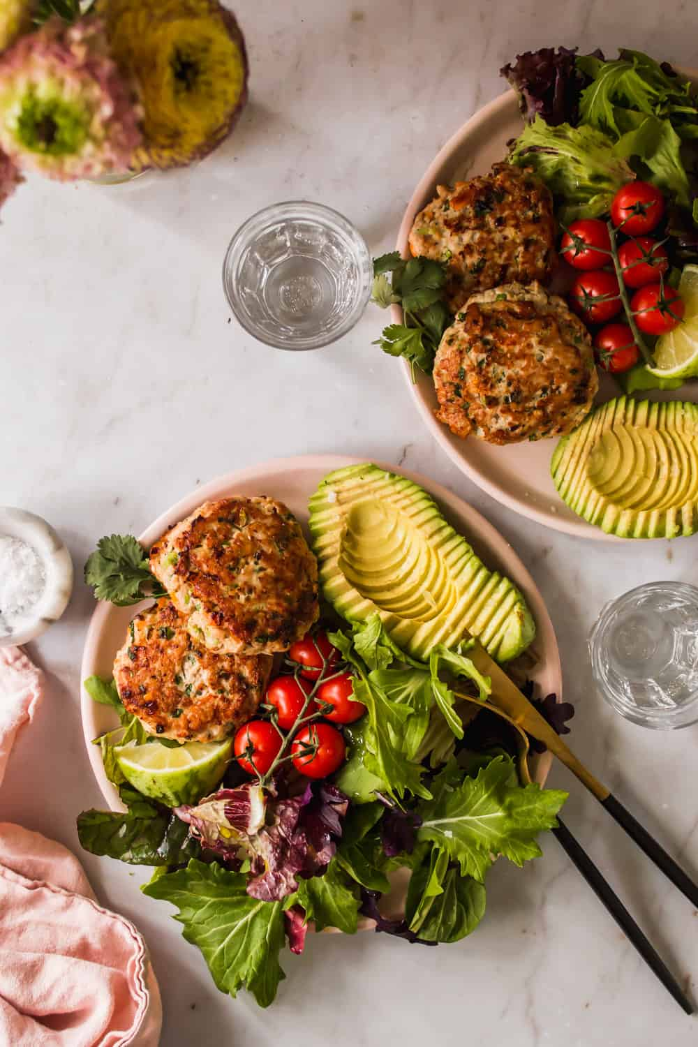 2 pink plates with salad, chicken burgers, and avocado on each