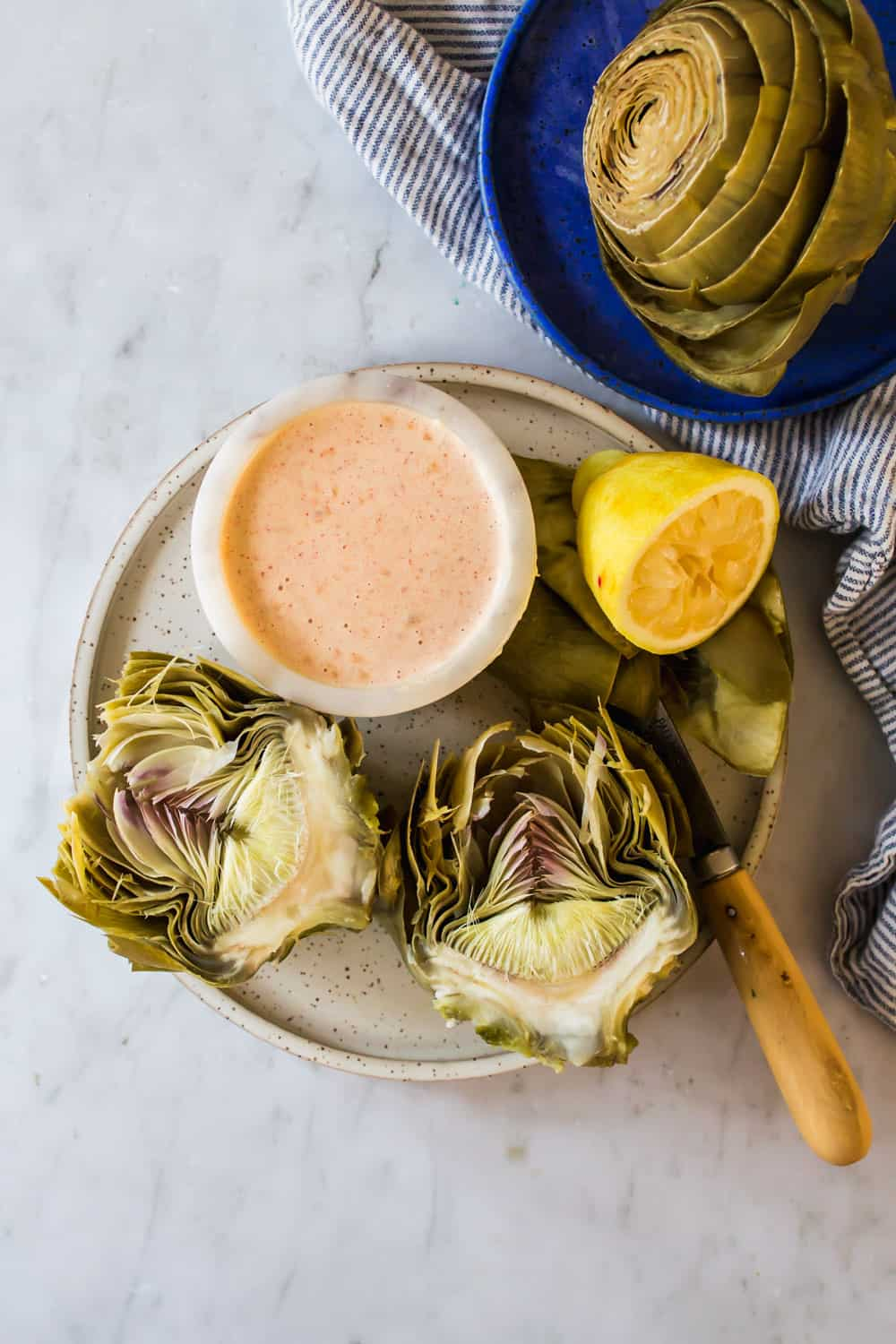 halved artichokes on a white plate next to dipping sauce and lemon