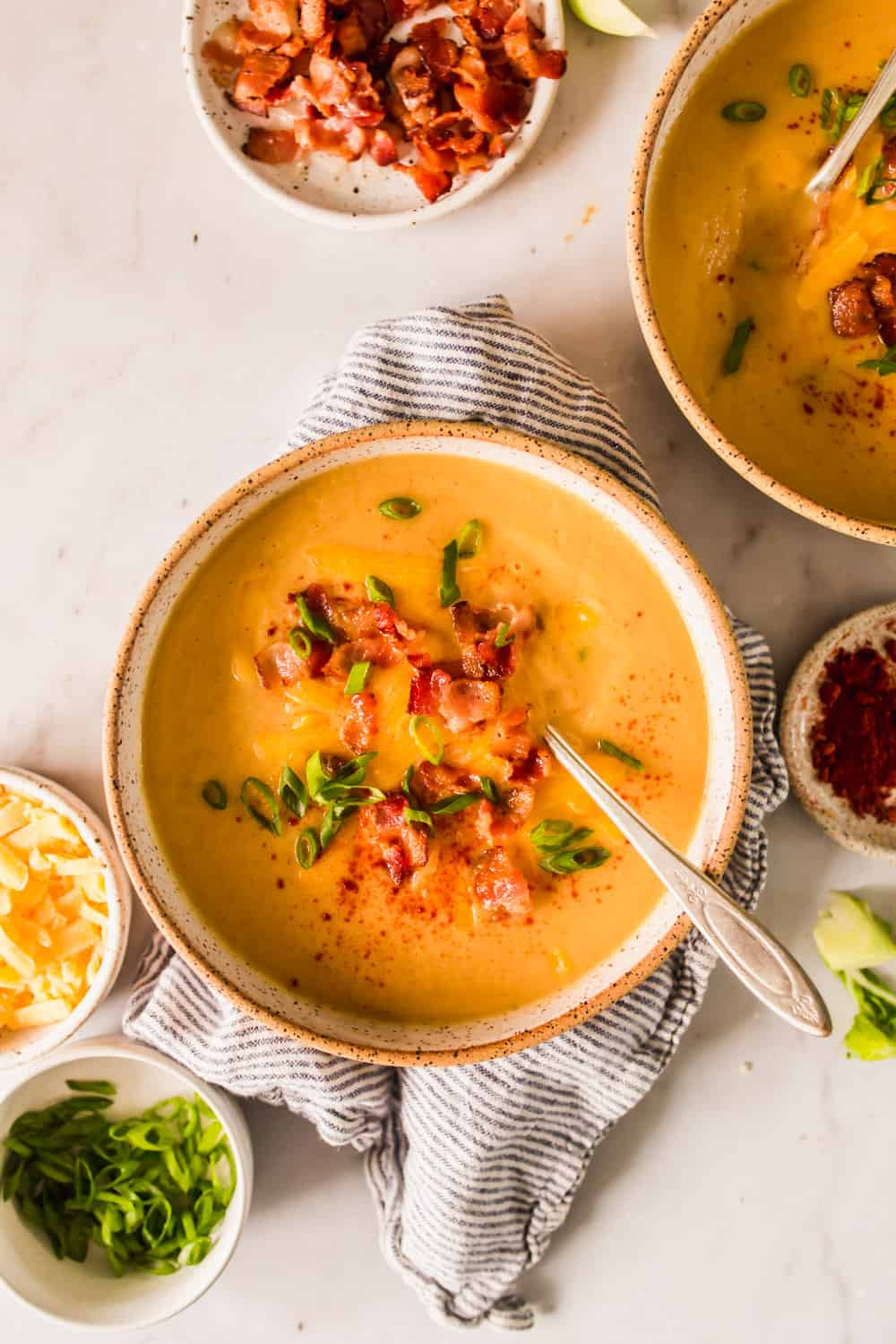 beige bowl filled with orange soup topped with bacon, scallions, and paprika