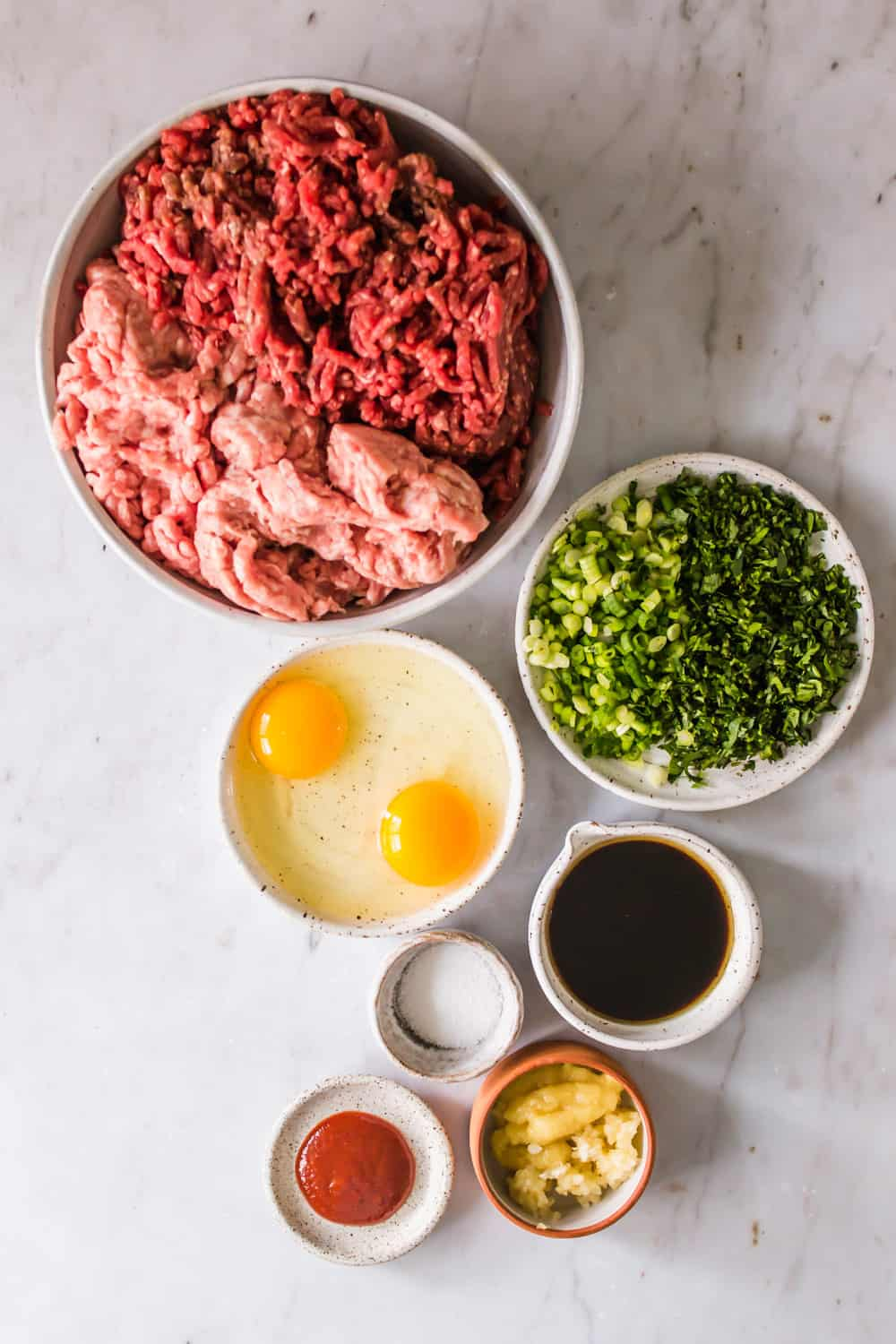 white bowls filled with ground meat, eggs, green herbs, sauce, and ginger