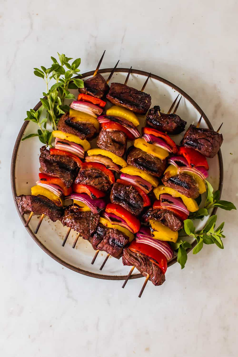 a white plate holding 4 grilled steak kabobs with red and yellow peppers and red onion
