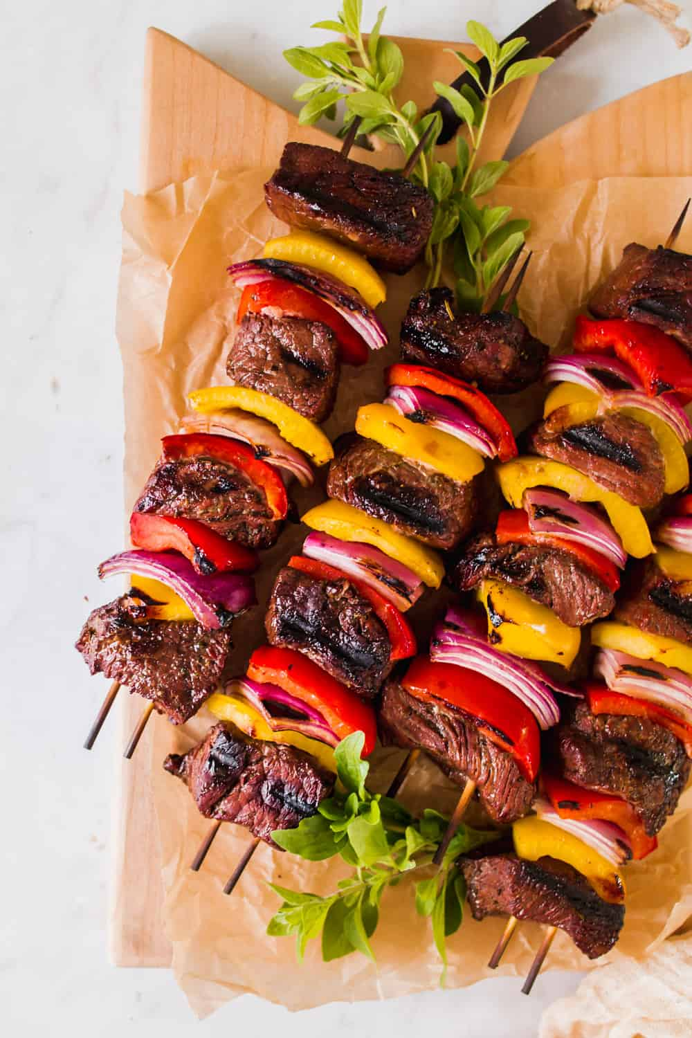 grilled steak kabobs with red and yellow peppers on a piece of brown paper