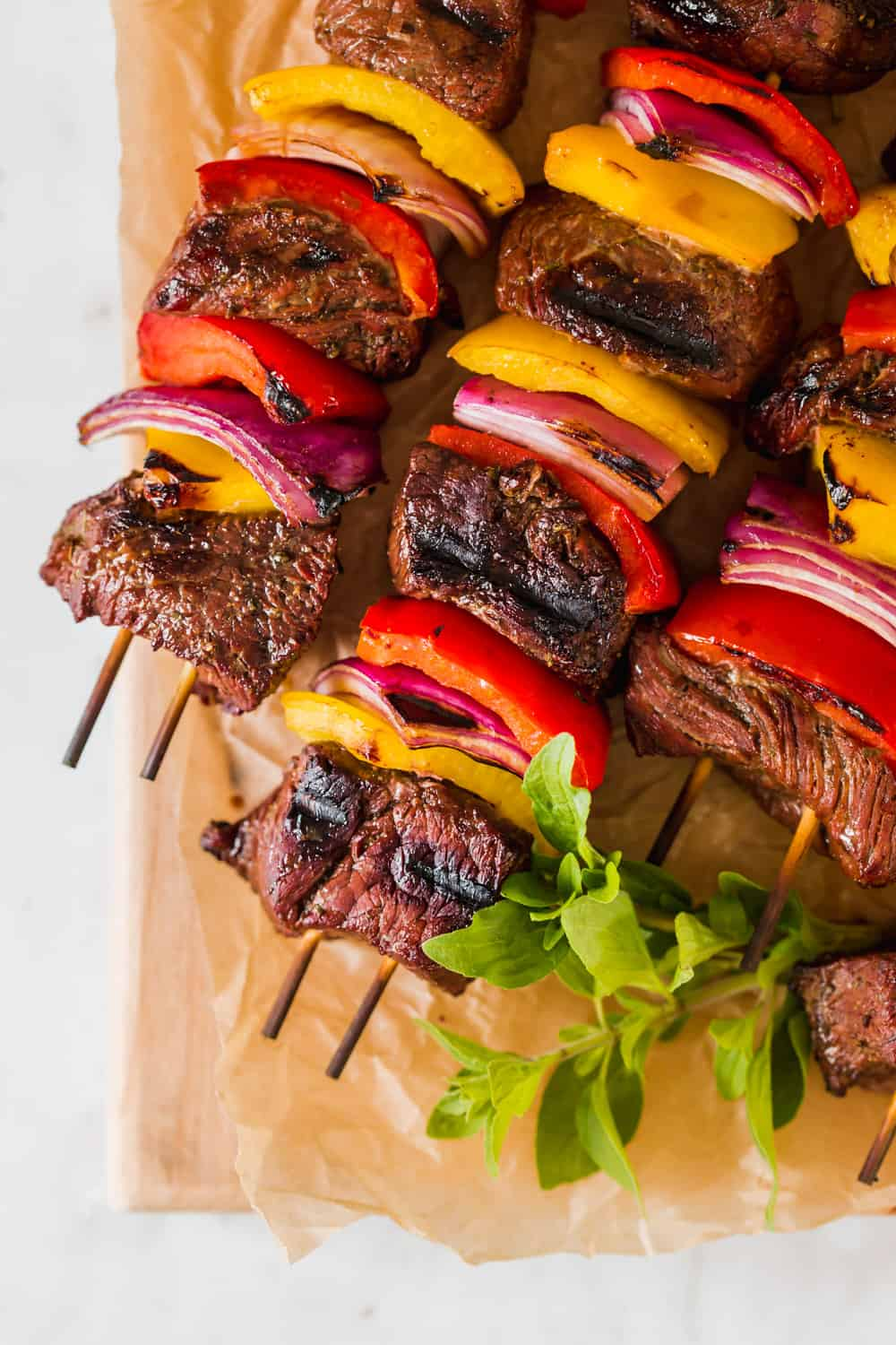 close up on grilled steak kabobs with red and yellow peppers on a piece of brown paper