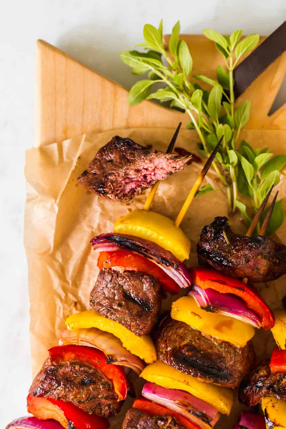 close up on a small piece of cut steak next to grilled beef kabobs