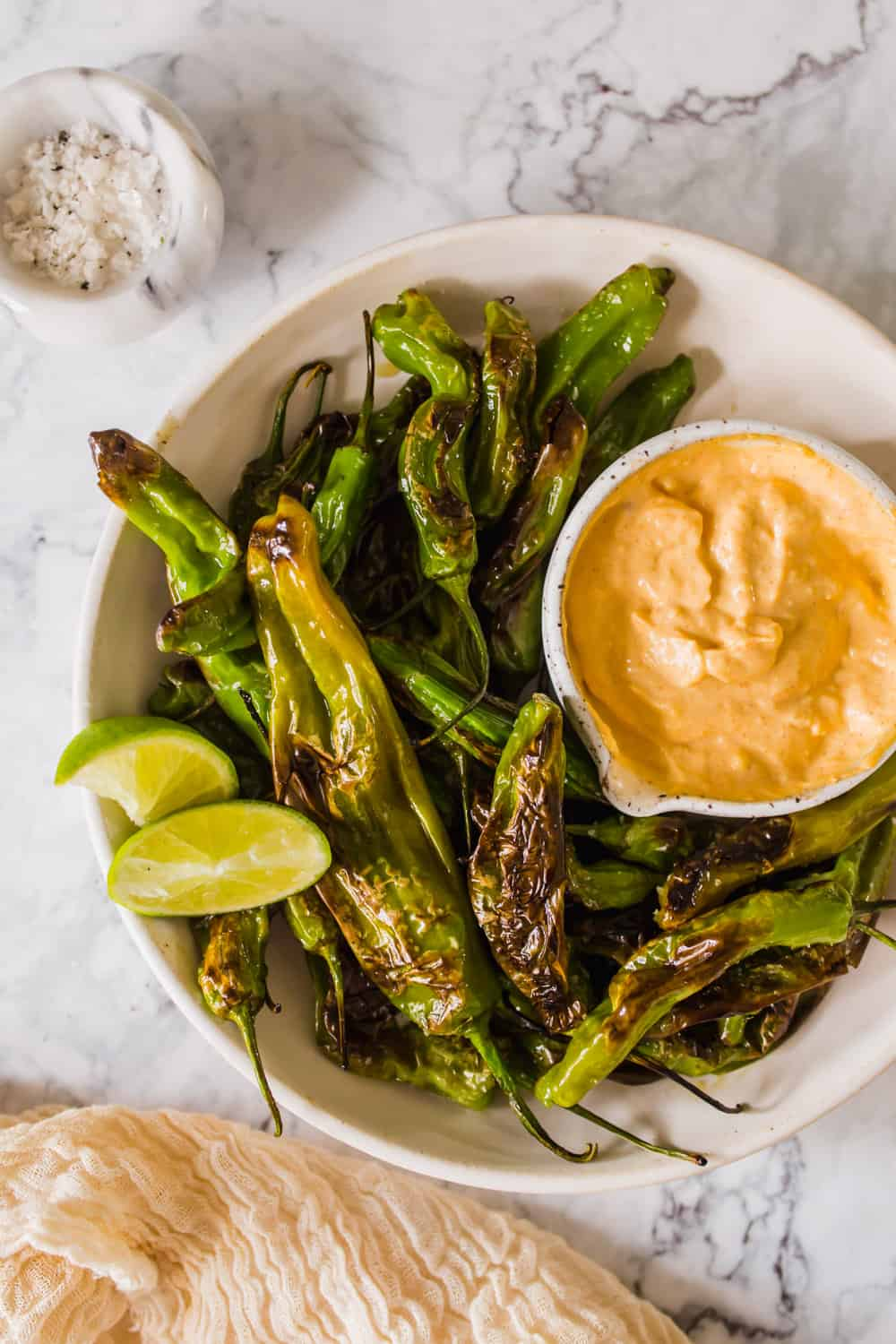 close up on a white bowl filled with charred green peppers and orange dipping sauce