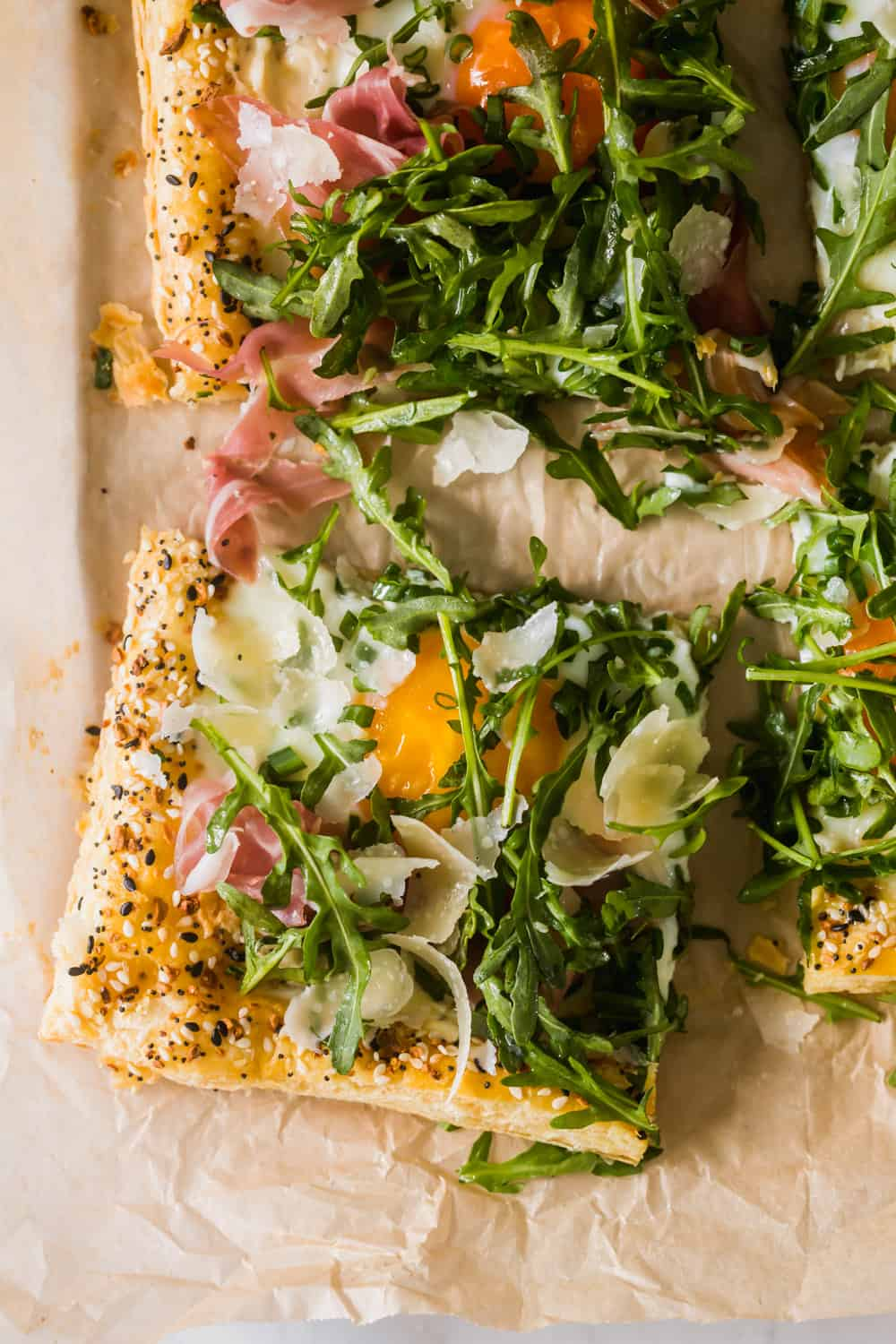 close up on a slice of baked puff pastry with a baked egg, prosciutto, and arugula on top