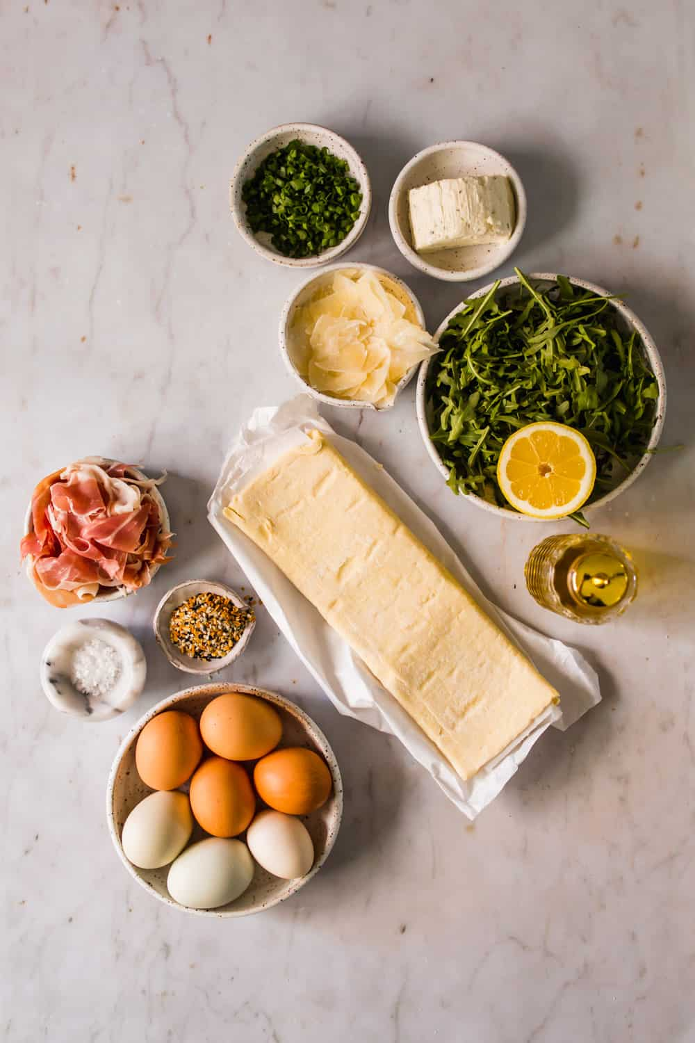 small white bowls with greens, cheese, herbs, meat, eggs, and seasonings next to a large piece of raw puff pastry