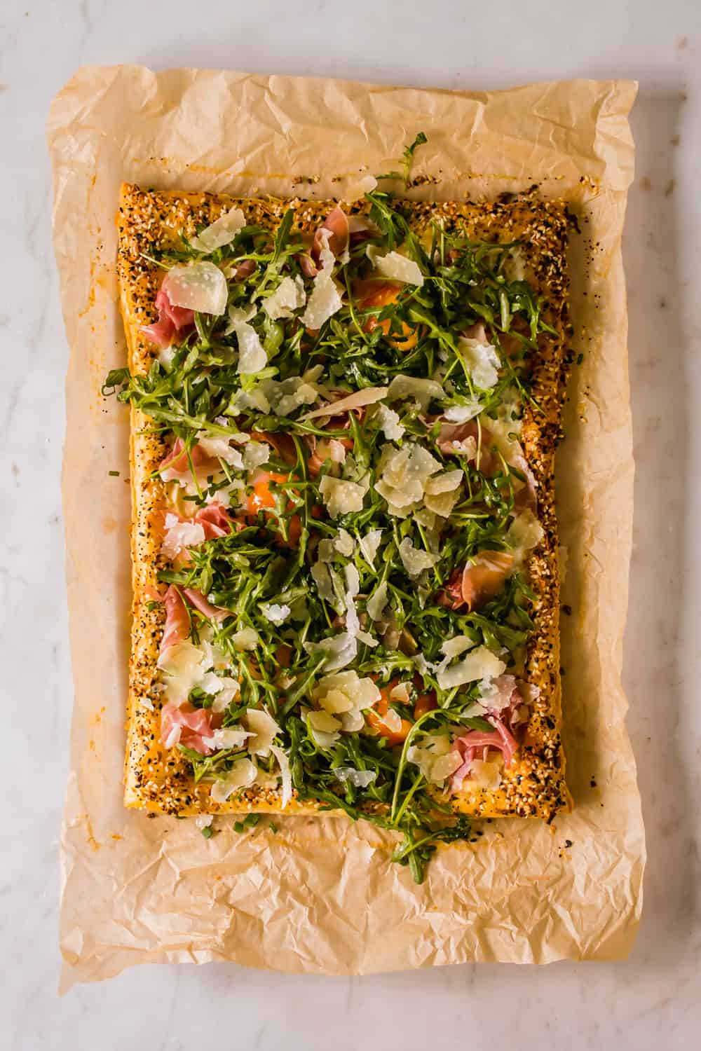 a large baked egg tart on parchment paper topped with prosciutto, arugula, and cheese