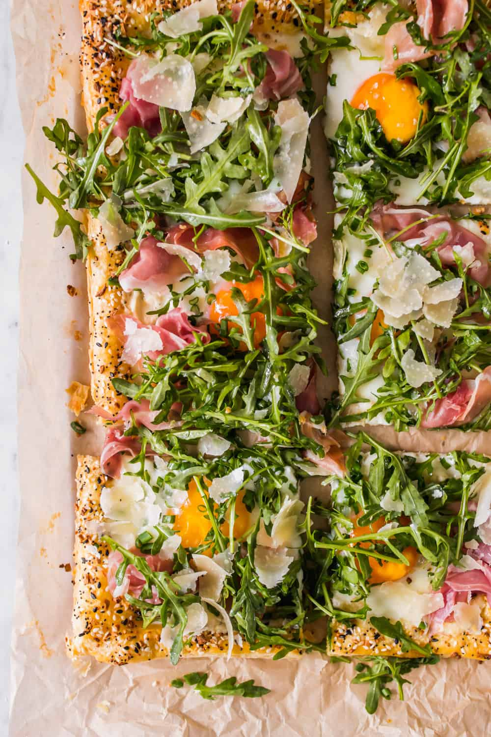baked puff pastry tart on parchment paper topped with baked eggs, prosciutto, and arugula