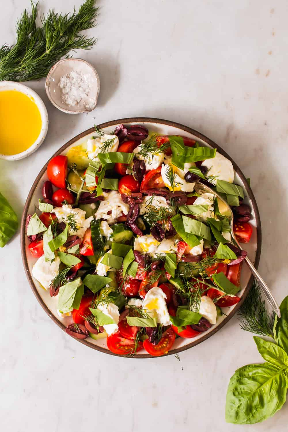 tomato, cheese, and cucumber salad in a large white bowl