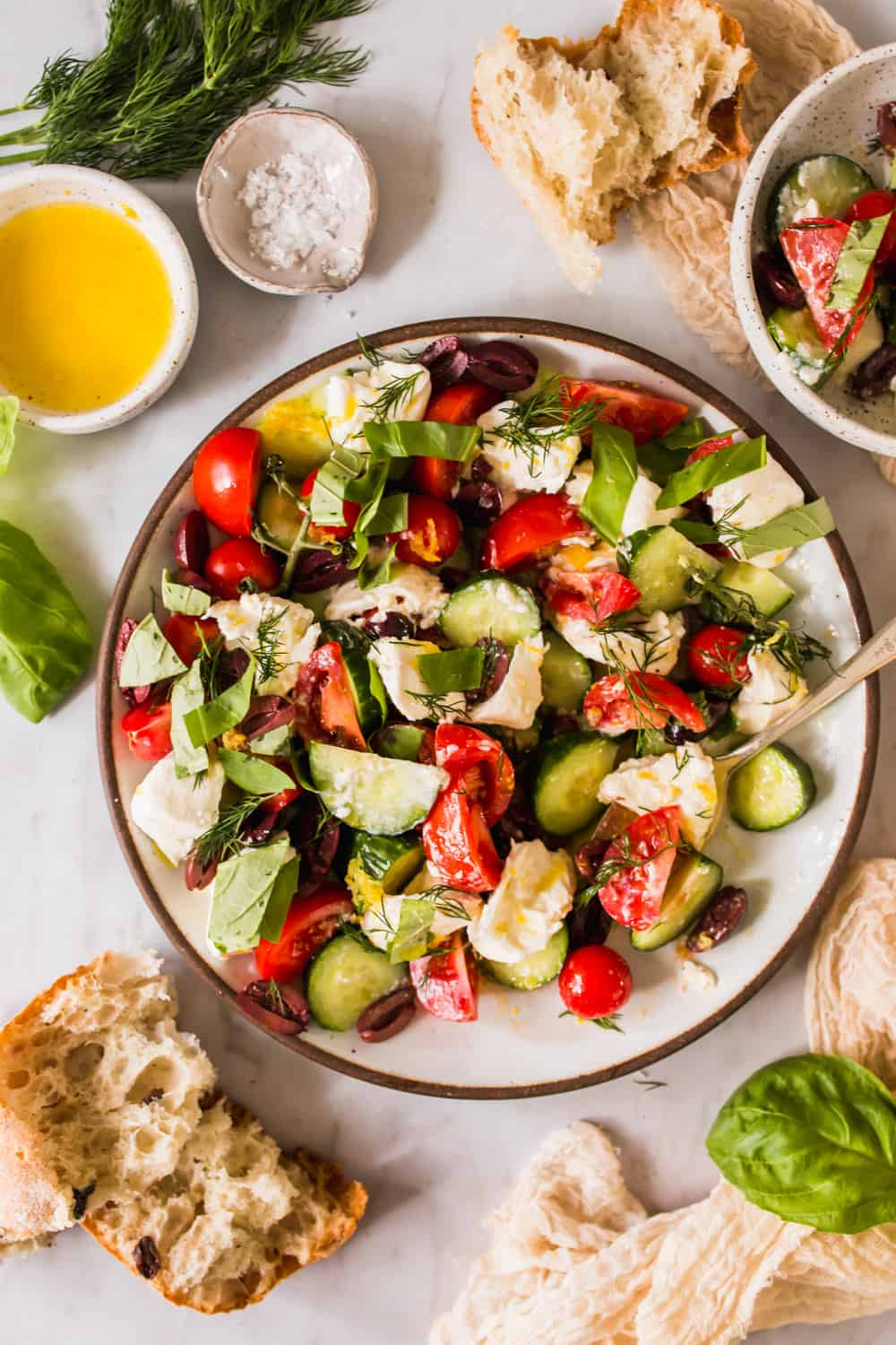 tomato, cheese, and cucumber salad in a large white bowl next to torn pieces of bread