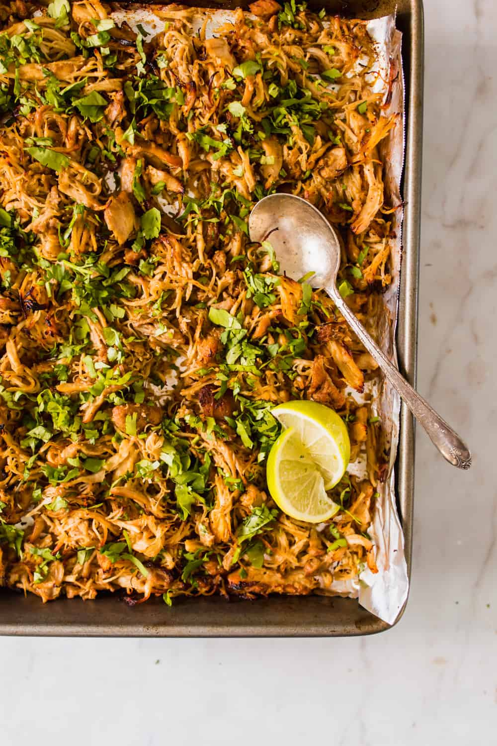 sheet pan filled with browned shredded chicken with herbs and lime wedges on top