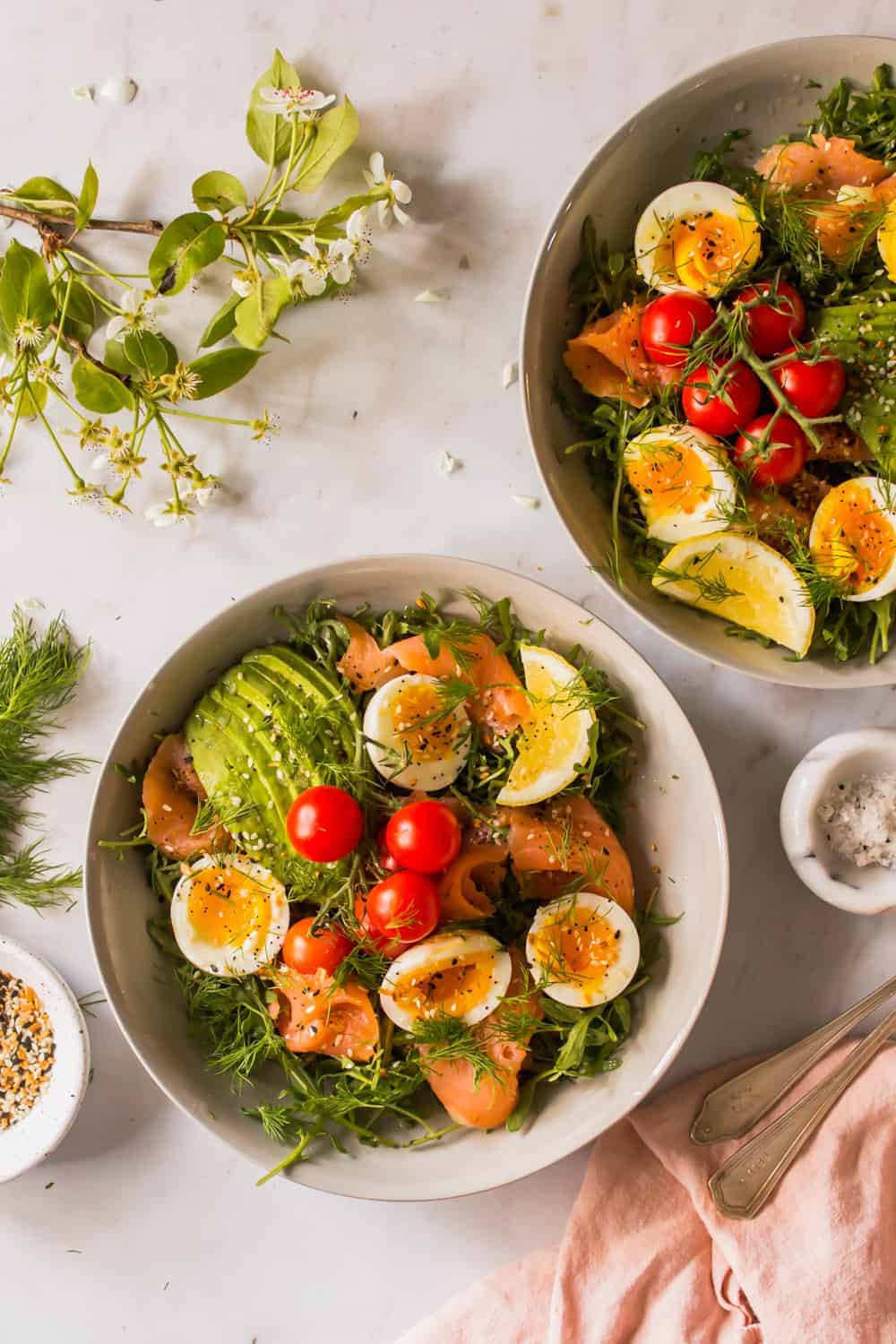2 white bowls of salad topped with eggs, tomatoes, salmon, and avocado
