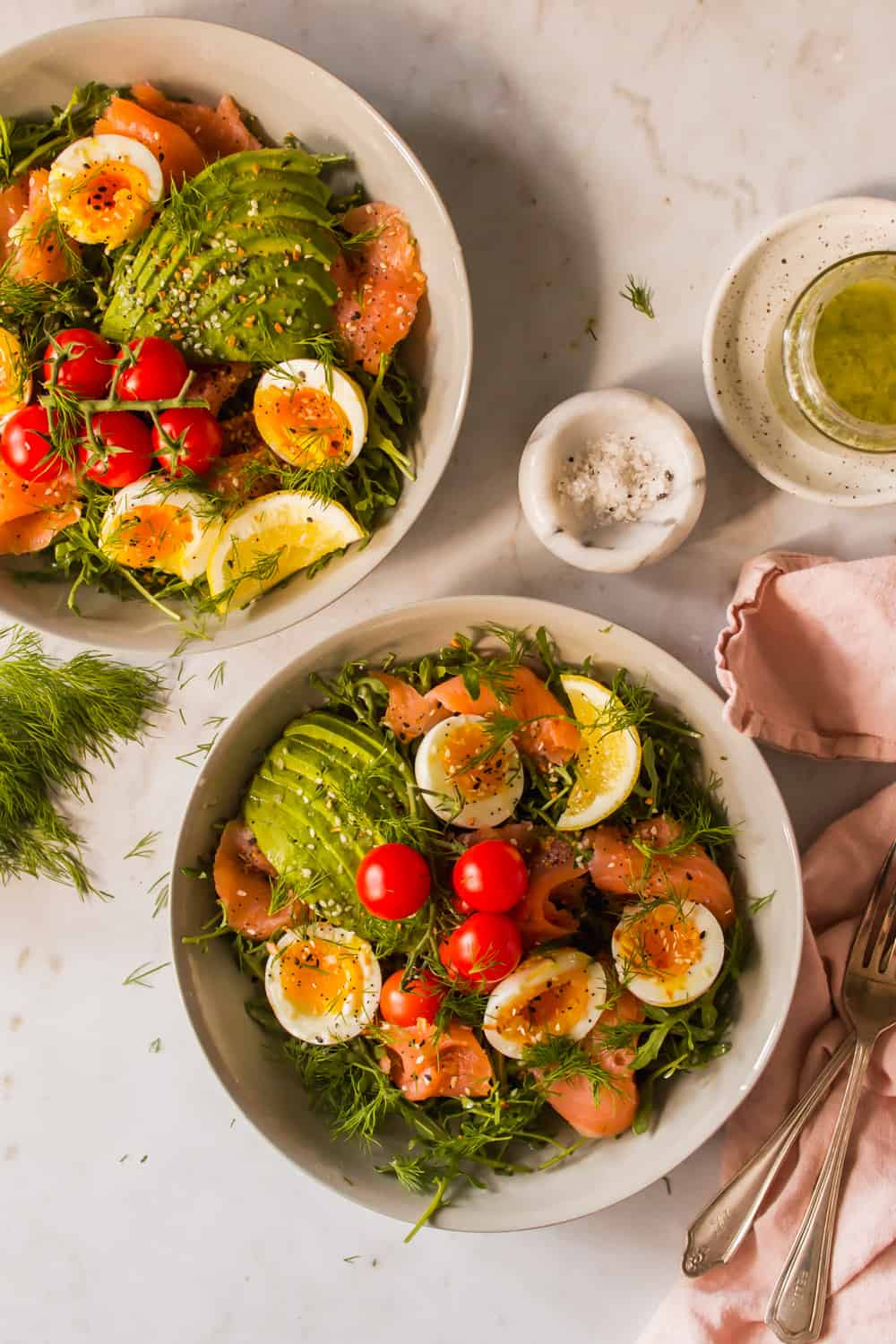 white bowls of salad topped with eggs, tomatoes, avocado, and salmon