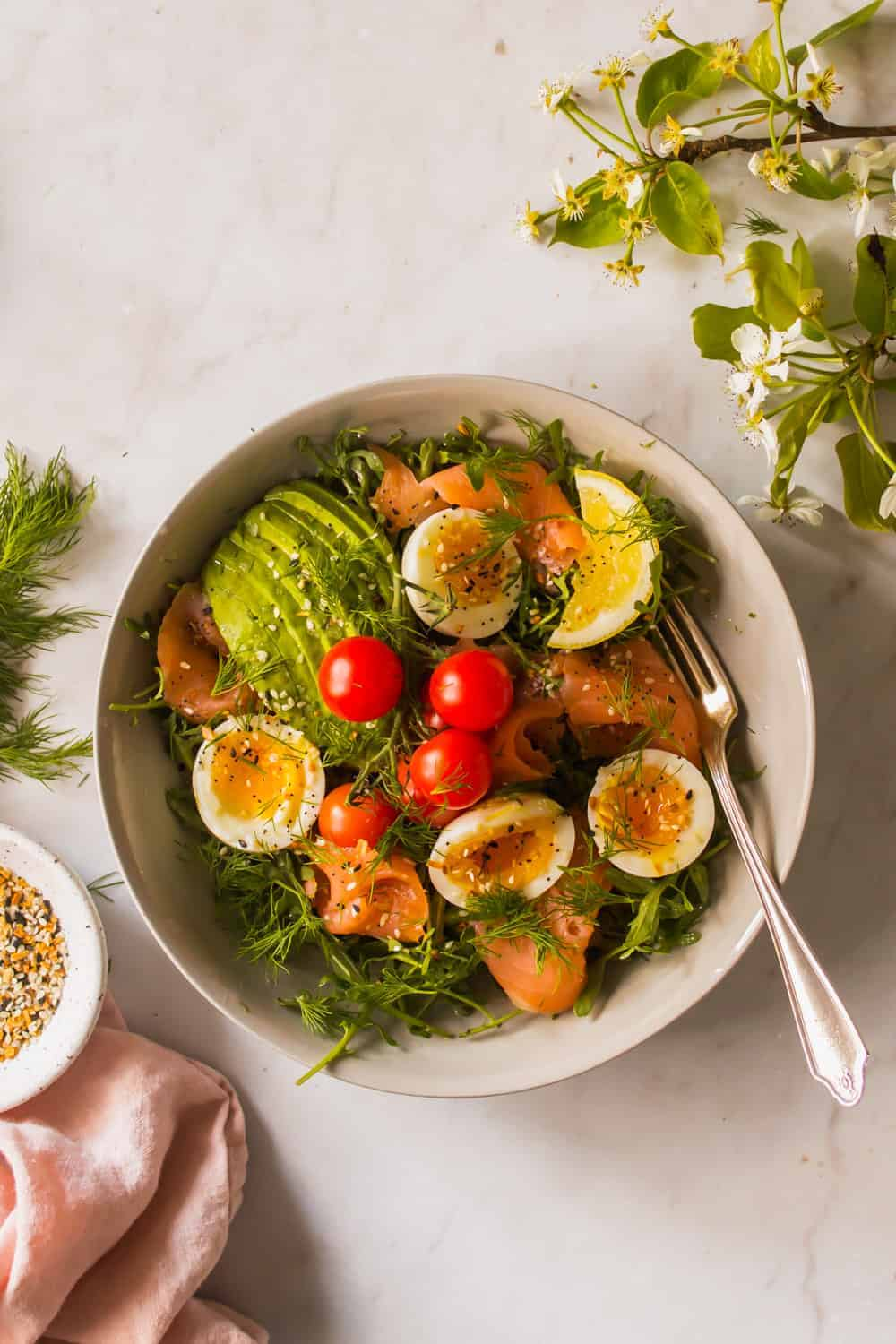 white bowl of salad topped with eggs, tomatoes, salmon, and avocado