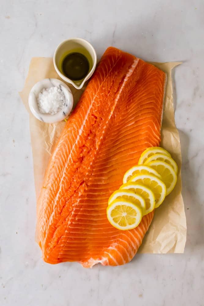 raw salmon filet on paper, next to lemon slices, salt and oil