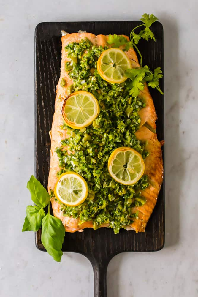 overhead view of a salmon fillet dressed in green sauce and lemon slices on a wood board