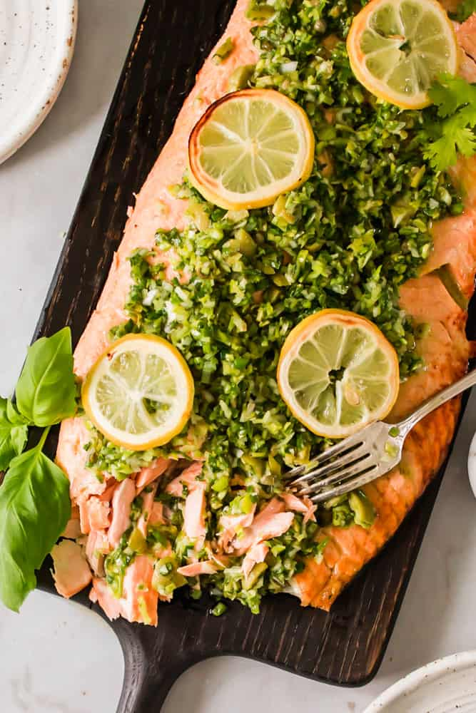 fork breaking up a salmon filet dressed in a green sauce and lemon slices