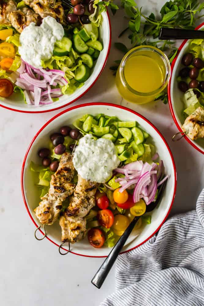 3 white bowls with salad, white sauce, and grilled chicken next to a jar fo yellow liquid