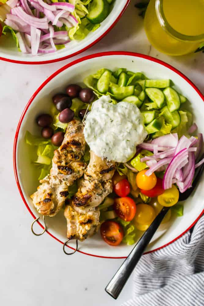 close up on a green salad topped with vegetables, white sauce, and grilled chicken in a white bowl