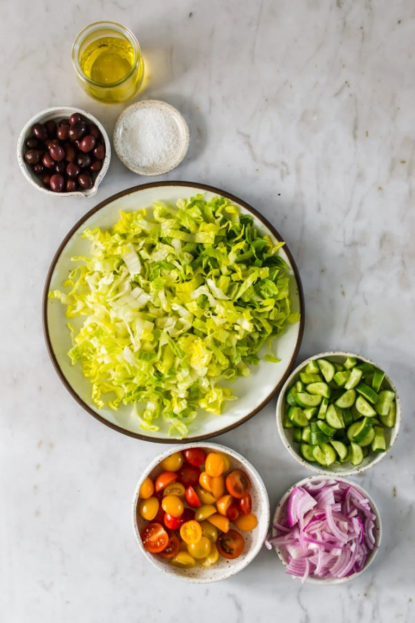white bowls holding lettuce, olives, cucumber, red onion, and tomatoes