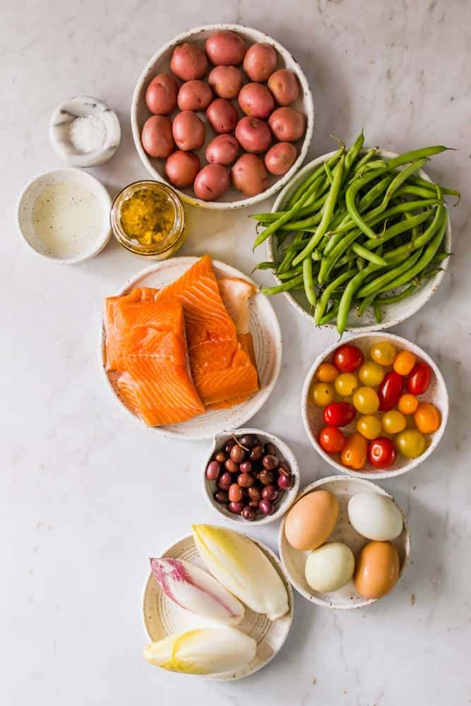 small white bowls holding raw salmon, oil, potatoes, green beans, tomatoes, olives, eggs, and endive leaves