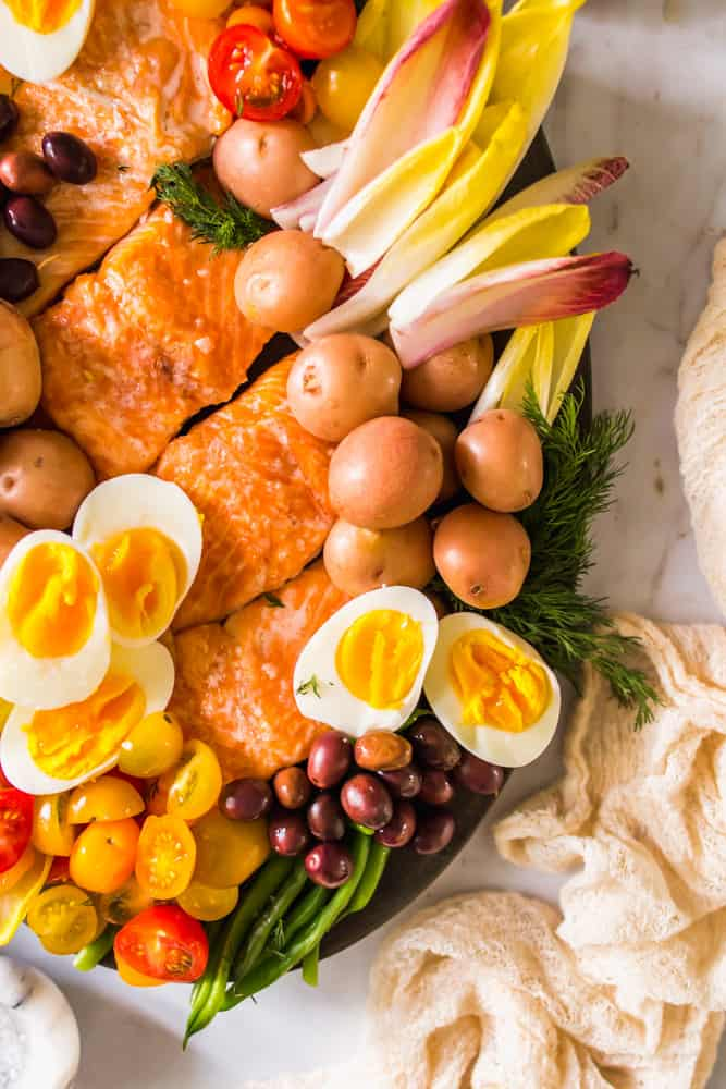 close up on a large black platter holding cooked salmon, endive leaves, potatoes, eggs, olives, and tomatoes