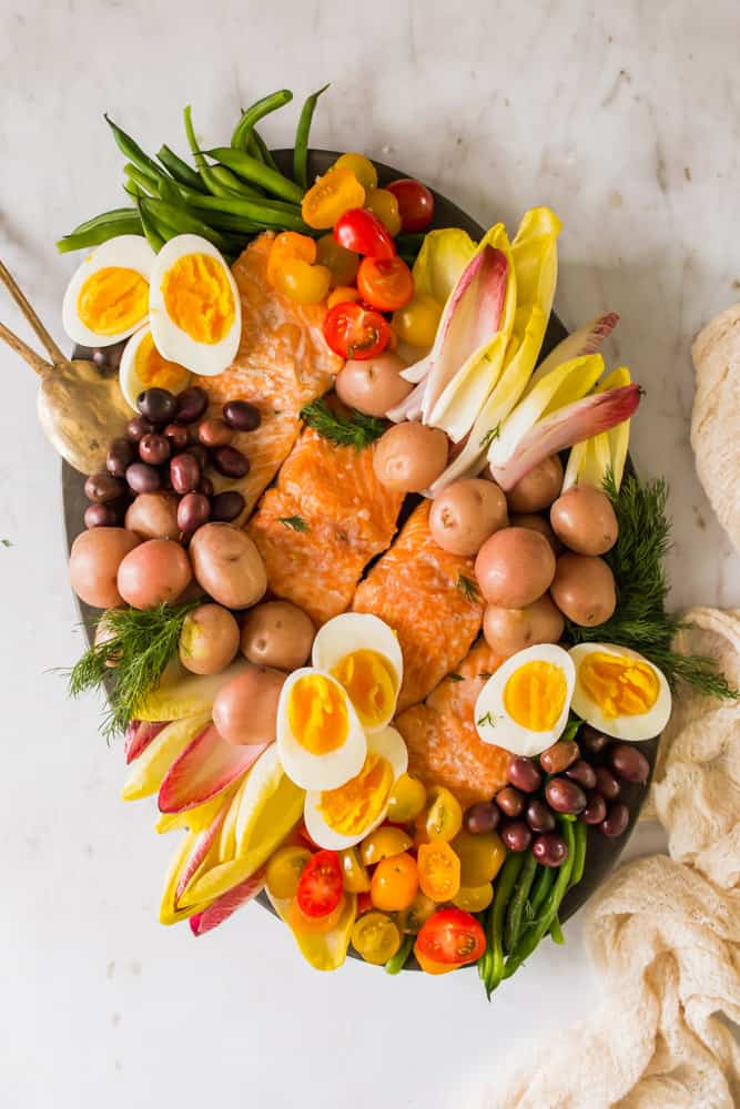 large black platter holding cooked salmon, endive leaves, potatoes, eggs, olives, and tomatoes