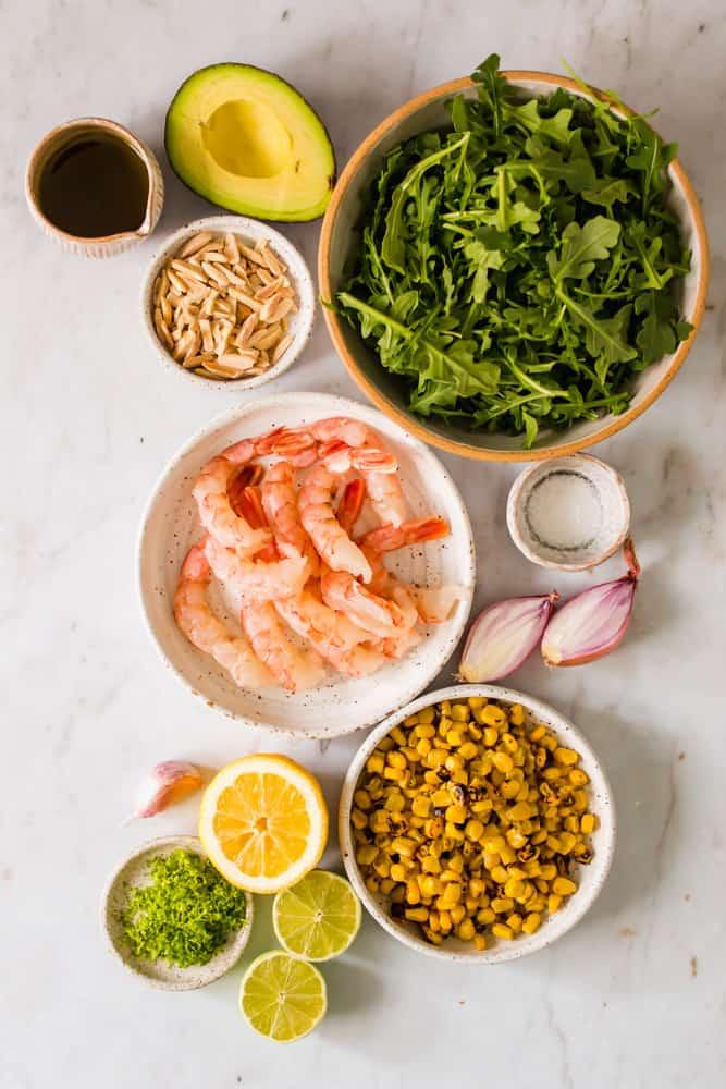 white bowls holding raw shrimp, arugula, corn, lime zest, and almonds next to shallots and lemon