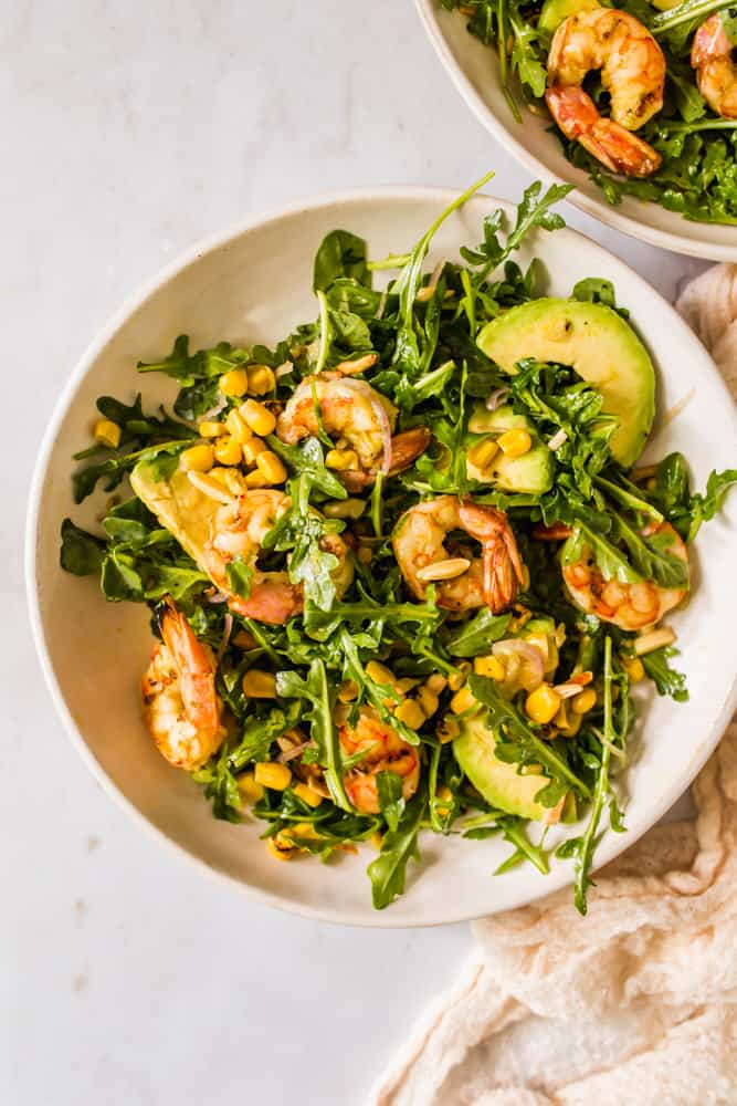 large green salad with shrimp, arugula, avocado, and corn in a white bowl