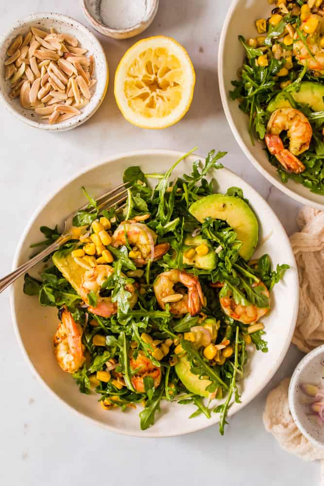 2 large green salads with shrimp, arugula, avocado, and corn in white bowls next to slivered almonds and lemon