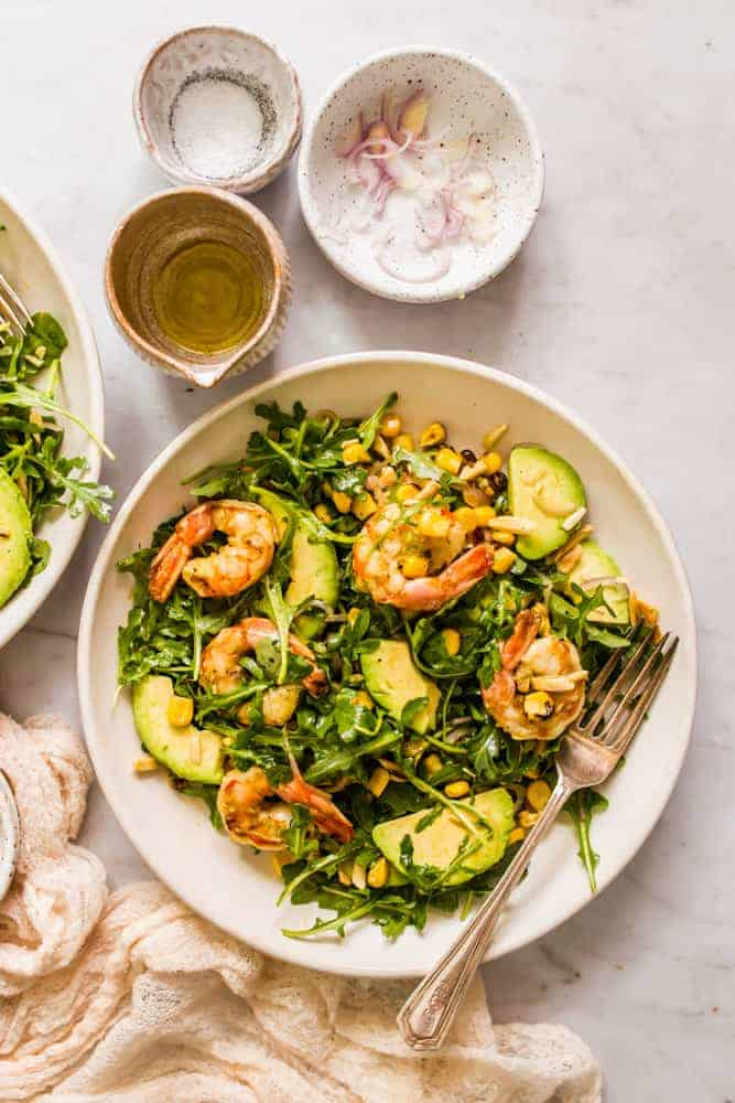 large green salad with shrimp, arugula, avocado, and corn in a white bowl next to small bowls holding shallots and dressing