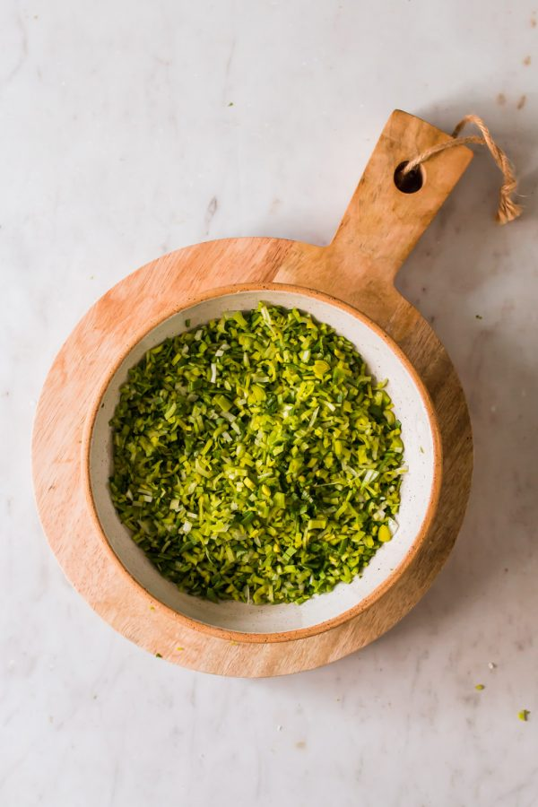 a green chopped herb sauce in a white bowl on top of a wood board
