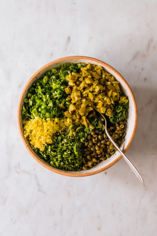 white bowl with chopped green herbs, lemon, and capers