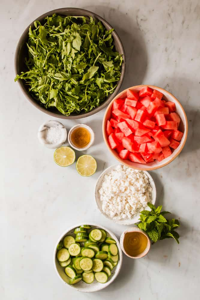 multiple bowls filled with ingredients for a watermelon salad.