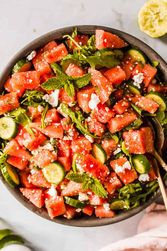 Close up of brown bowl filled with watermelon and cucumber salad.