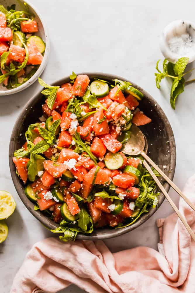 Cubed watermelon and cucumber with greens and mint in a brown bowl with two serving spoons and a small white side dish of salad.