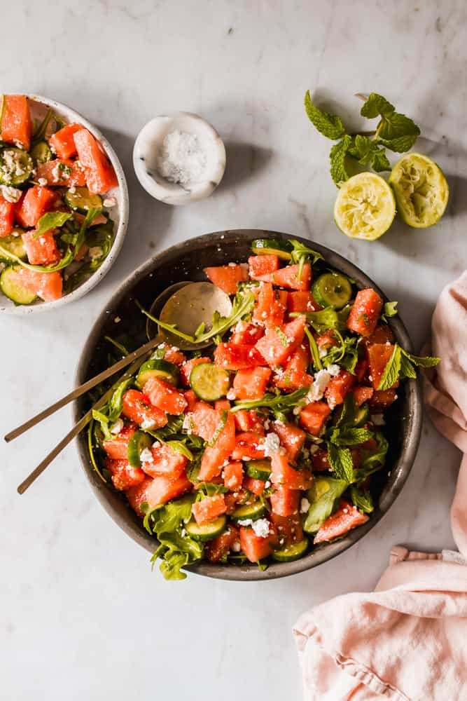 Cut up watermelon and cucumber with greens and mint in a brown bowl with two serving spoons and a small white side dish of salad.