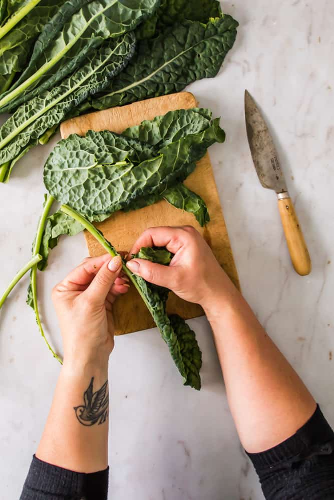 womans hands peeling kale leaves from the stem