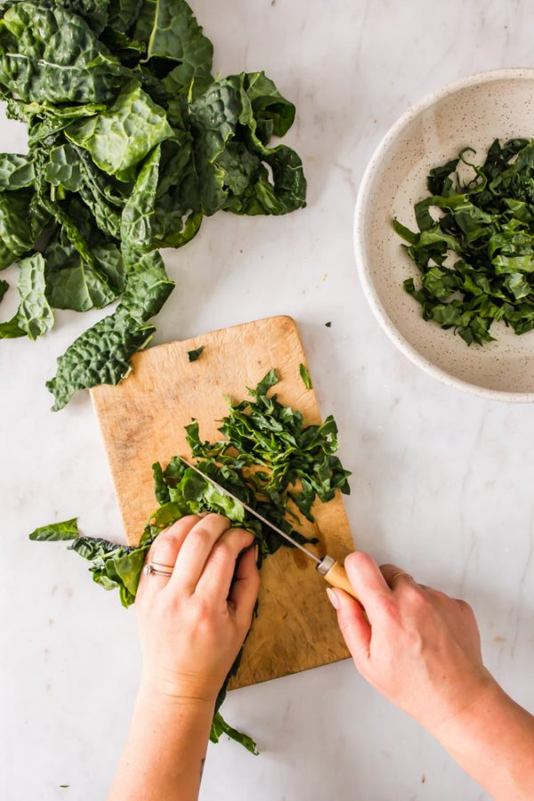 womans hands chopping kale on a wood board