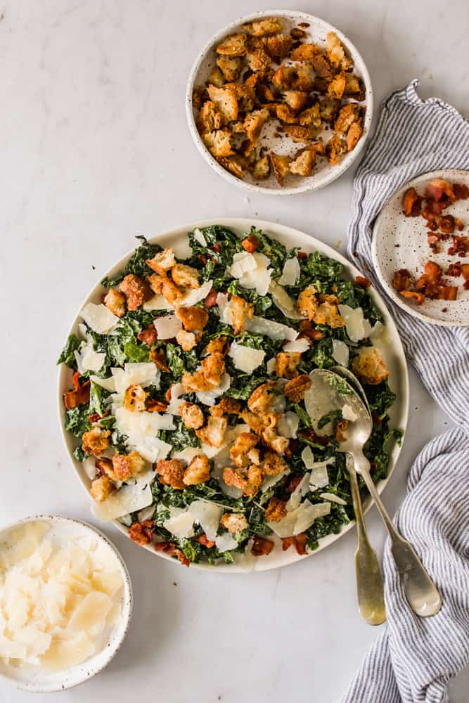 large caesar salad in a white bowl next to small bowls of croutons, cheese, and bacon
