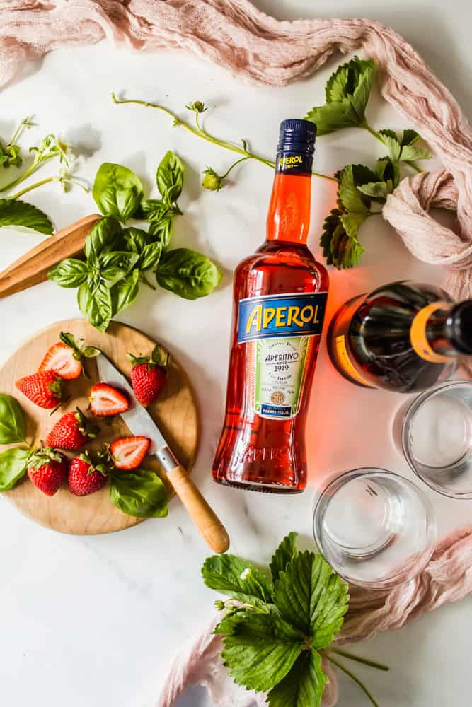 bottles of Aperol and prosecco next to basil leaves and a wood board with strawberries
