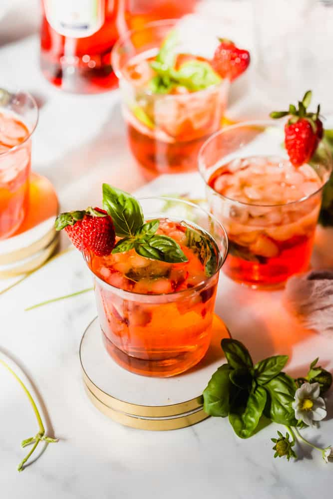 red drinks with ice, strawberries, and basil on white coasters