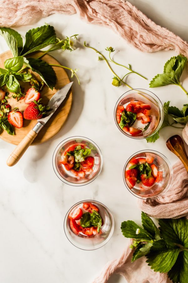 4 glasses holding strawberry slices and basil leaves next to a knife cutting strawberries on a wood board