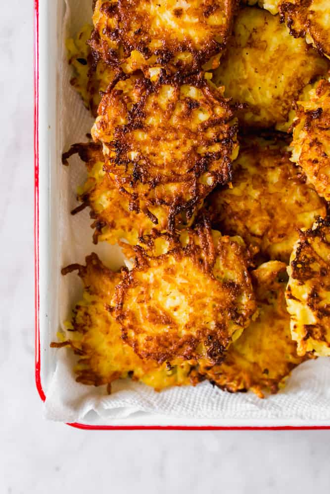 close up on golden brown cooked potato latkes in a white and red baking dish