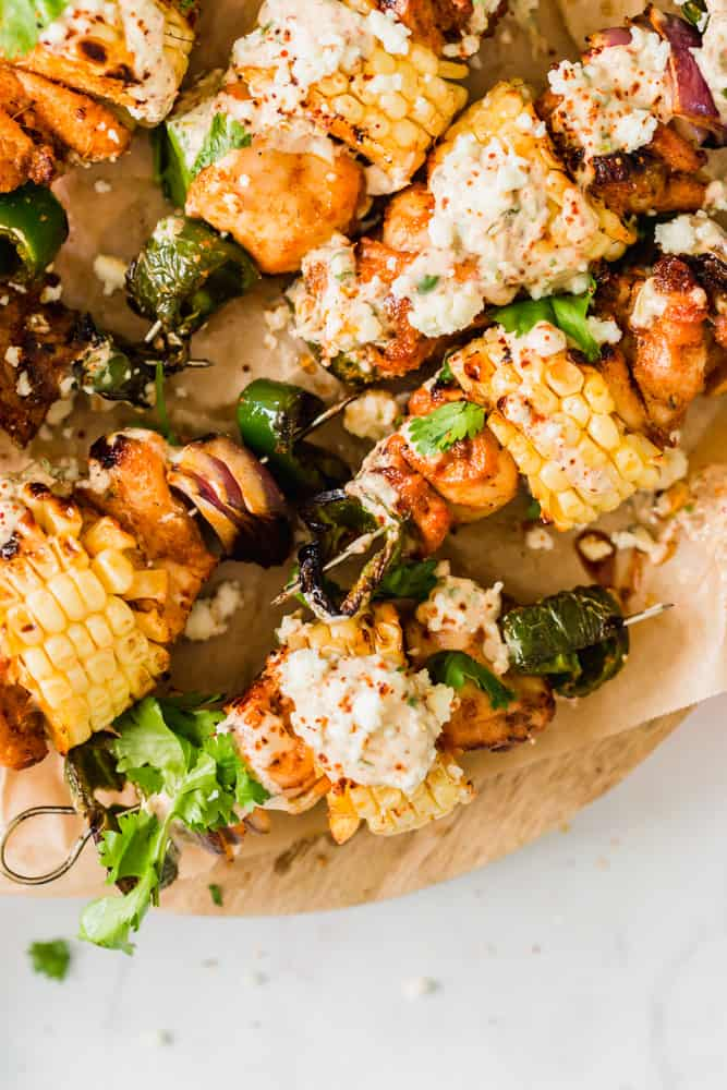 close up on corn and chicken skewers topped with white sauce on a wood board