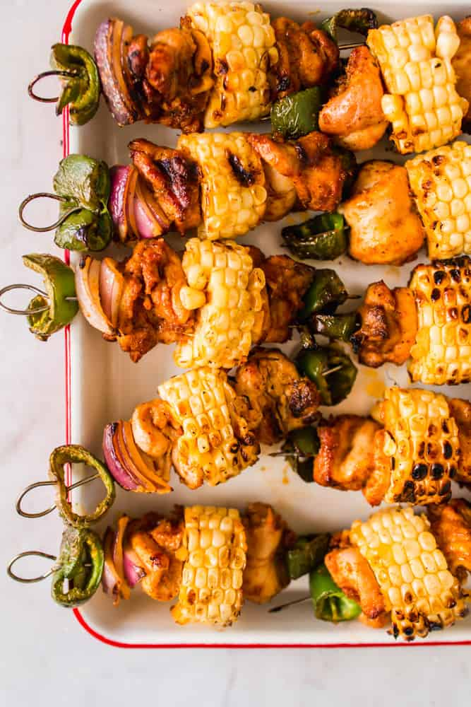 close up on corn and chicken skewers in a white baking dish