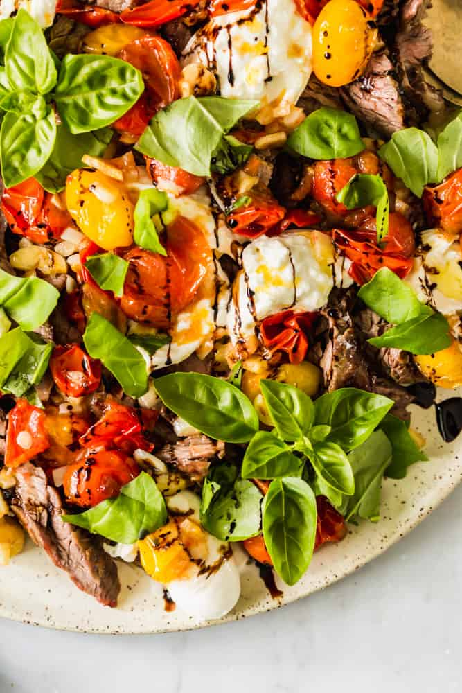 close up on cooked steak and tomatoes on a white platter topped with fresh basil leaves and white cheese